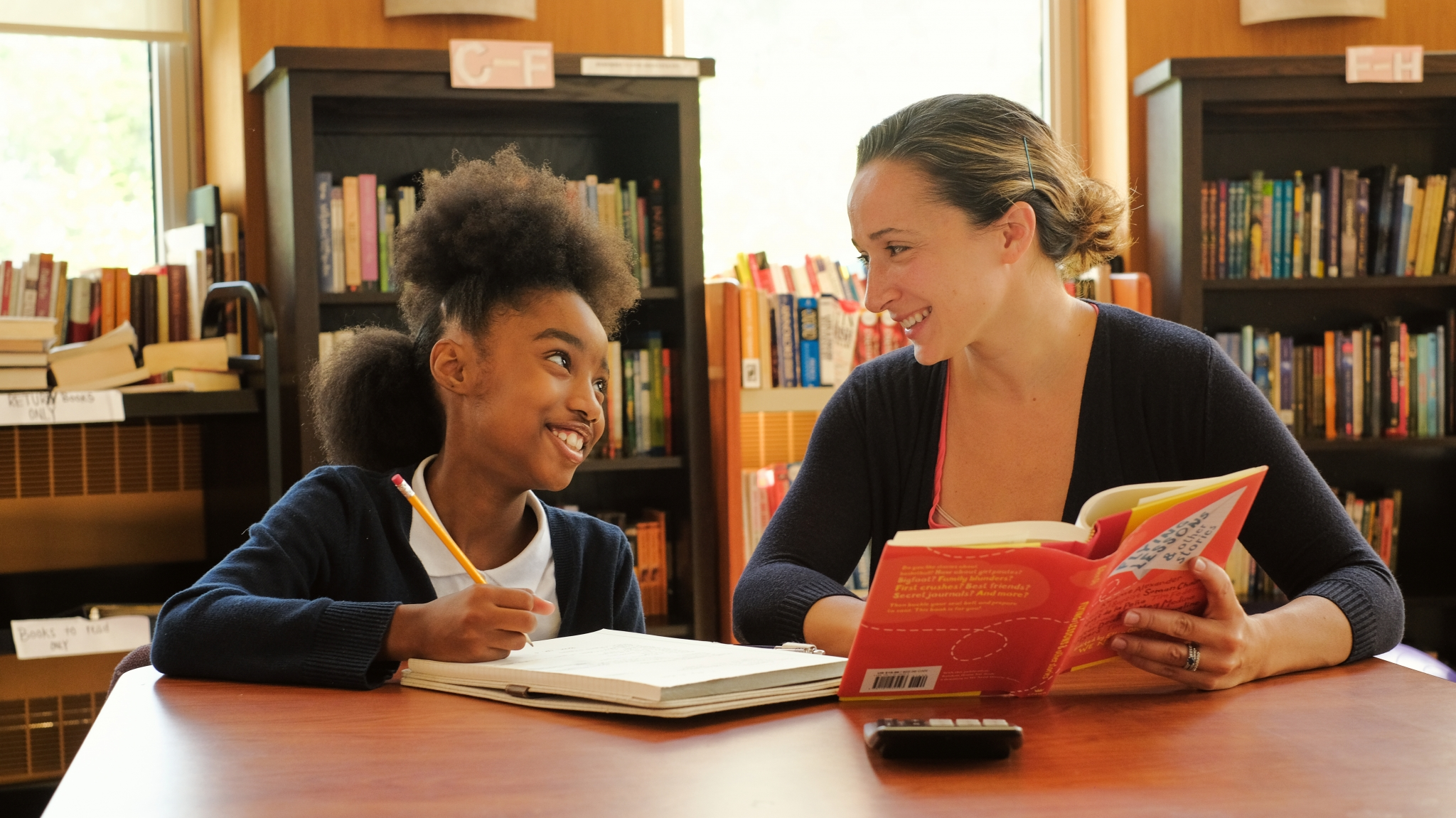 Young girl and female tutor smiling